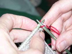 Draw the yarn on the right hand needle through the stitch on the left hand knitting needle