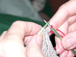 Slip the old stitch off the left knitting needle by pulling the right hand needle to the right.